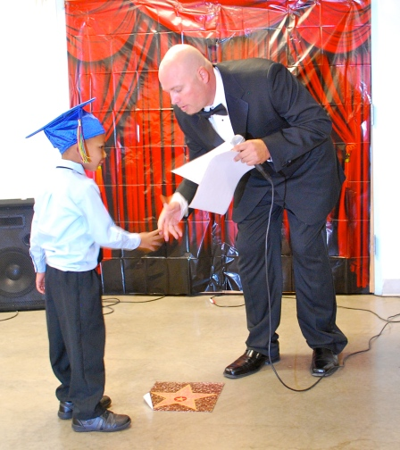 Graduate shakes Preschool Director Brad Dale's hand before receiving his Oscar.