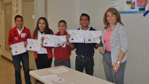 Students pose with Principal Munguia displaying their certificates.