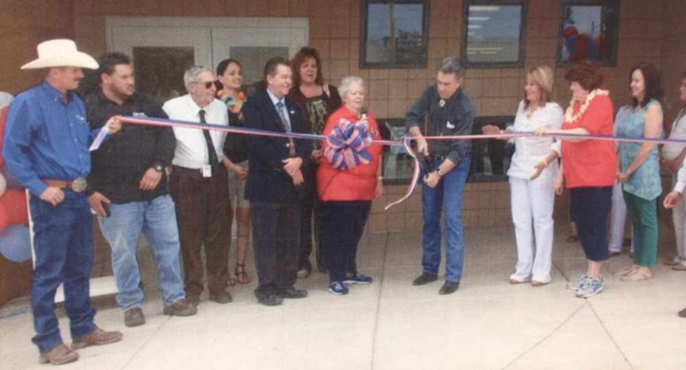 Veda Phelps, Don Derrick, and Marcela Munguia (pictured center) preside over the ribbon cutting.