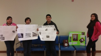 6th graders pose beside their research posters.