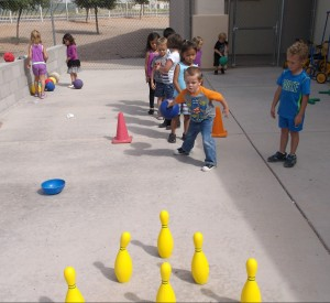 Preschooler bowls during heart healthy play.