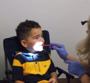 Preschooler smiles wide as his teeth are checked.