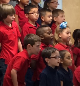 1st and 2nd grade students watch Ms. Dokken intently as they sing.