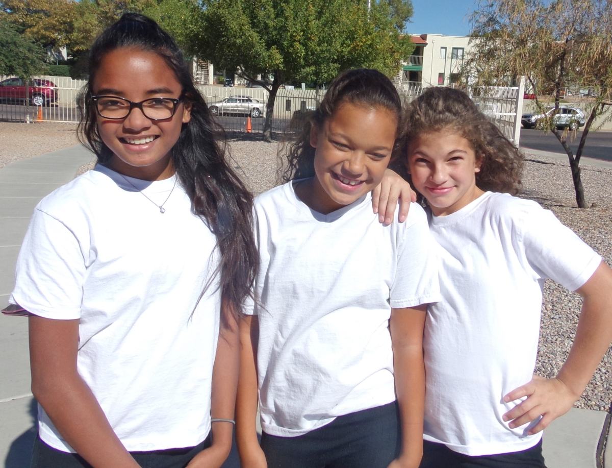 Three Middle School girls wearing match white shirts