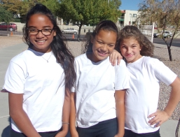 Three Middle School girls wearing match white shirts