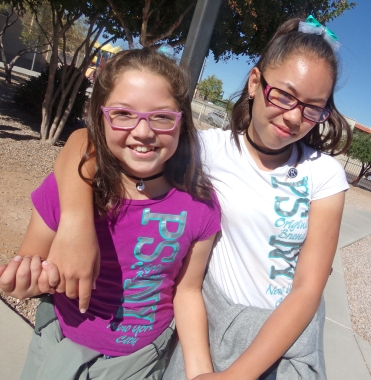 Two female middle school students wearing matching shirts