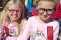 Two young girl students dressed in matching pink kitten shirts for twins day