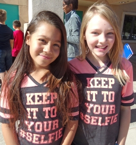"Two young female students wearing matching shirts saying ""Keep it to your #Selfie"""