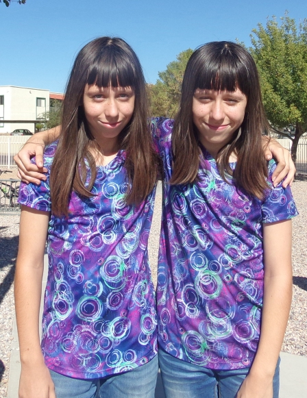 Twin female students wearing matching purple shirts