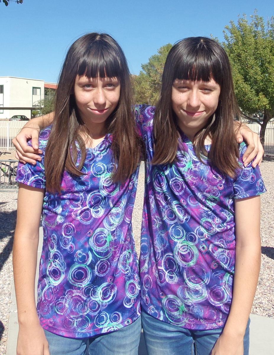 Twin female students wearing matching purple shirts