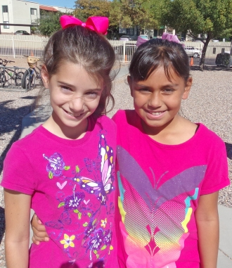 Two female Middle School students wearing matching pink butterfly shirts